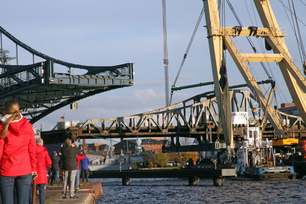 """Schwimmkran """"Enak"""" bugsiert die ausgehängte Deichbrücke durch die Kaiser-Wilhelm-Brücke. Foto: Imke Zwoch"""